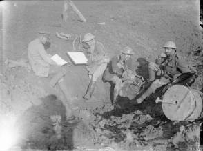 Officiers britanniques étudiant des cartes et utilisant le téléphone, sur la ligne de front en octobre 1916. [Royal Artillery officers study maps and use a field telephone in a forward observation post in a shell hole near the front line, Flers, October 1916.] © IWM (Q 1430)