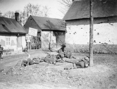 Troupes britanniques se reposant en bord de route à Forceville, en 1918 [Battle of the Lys. Exhausted British troops resting on the side of the Forceville Road.] © IWM (Q 366)